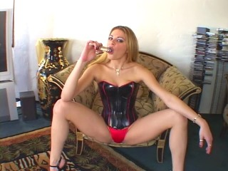 Kinky blonde in a rubber corset and red panties spanks herself and twists a glass dildo in and out of her ass
